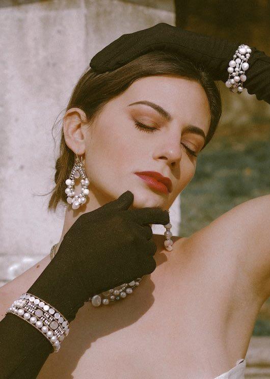 Una bella donna con guanti lunghi neri in un giardino italiano indossa splendidi gioielli Ziio fatti di perle, madreperle della collezione chiamata Shinju. Shinju significa perla in giapponese